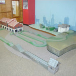 Wooden roadway exhibit with buildings and a Buffalo skyline.