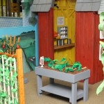 Farm exhibit at Explore & More, featuring toy vines, corn, tomatoes, and barn.