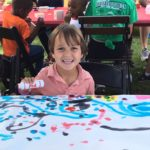 Smiling child draws with paint markers at Canalside.